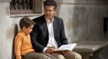 Father holding book sitting on bench with son (5-7)